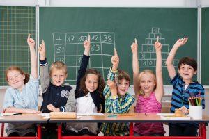 Cultura emprendedora en educación con niños entusiasmados en clase levantando la mano par acontestar