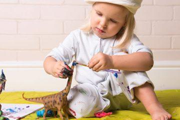 niño pintando dinosaurio para ejemplificar manualidades infantiles de dinosaurios