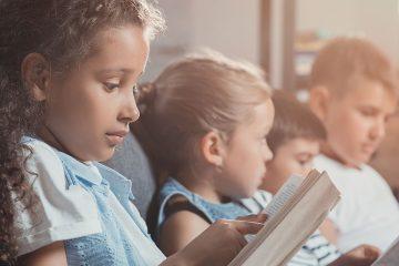 Imagen con niños y niñas leyendo libros