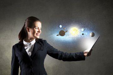Chica sosteniendo una tablet en la mano de la cual emerge el sistema solar para ilustrar la Semana Mundial del Espacio