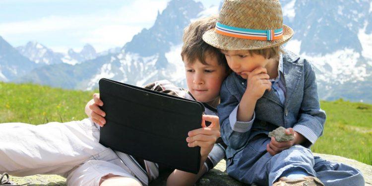 dos niños con un ipad en una montaña representando el u-learning