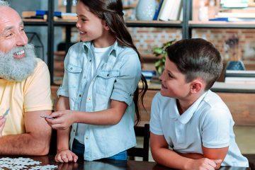 Un abuelo y sus dos nietos sonriendo y montando un puzle para ilustrar los beneficios educativos del puzle