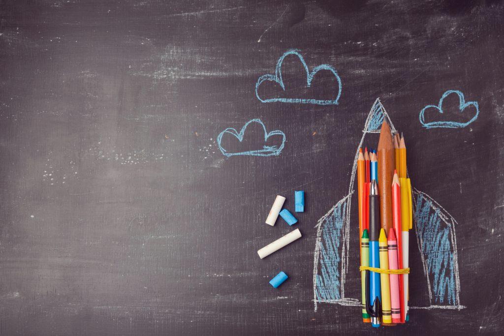 Pizarra con un cohete dibujado en tiza y relleno de lápices colores para ilustrar la fascinación por el espacio