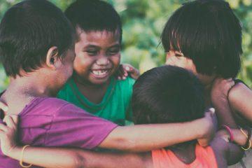 Cuatro niños sonriendo y abrazándose en círculo que ilustran la importancia de educar en la No violencia