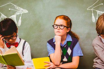 Dos niños y una niña con libros y actitud reflexiva para ilustrar la importancia de hacer filosofía desde pequeños
