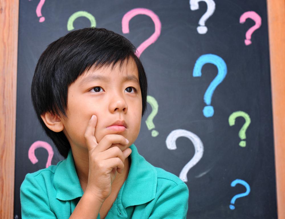 Niño pensando y una pizarra de fondo con interrogantes como ejemplo de hacer filosofía