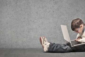 niño con una portátil más grande mirando internet