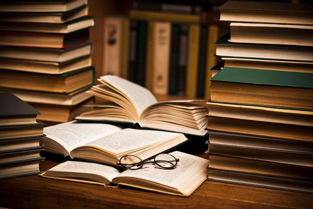Libros abiertos frente a los estantes de una librería ilustrando la historia de las librerías