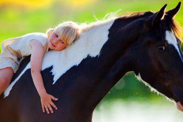 Niña abrazada a un caballo para ilustrar la fascinación infantil por los animales