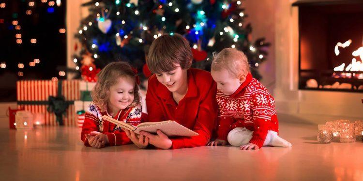 Tres niños leyendo con un árbol navideño de fondo para ilustrar las 10 recomendaciones de libros para estas navidades