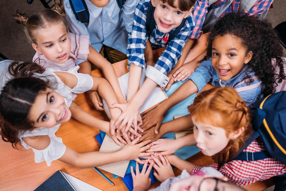 Niños con las manos unidas representando el trabajo en equipo para emprender