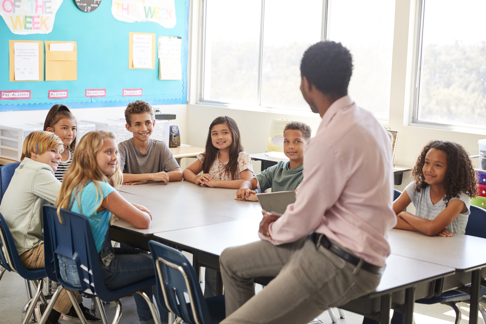 teacher with children in a table for work in groups