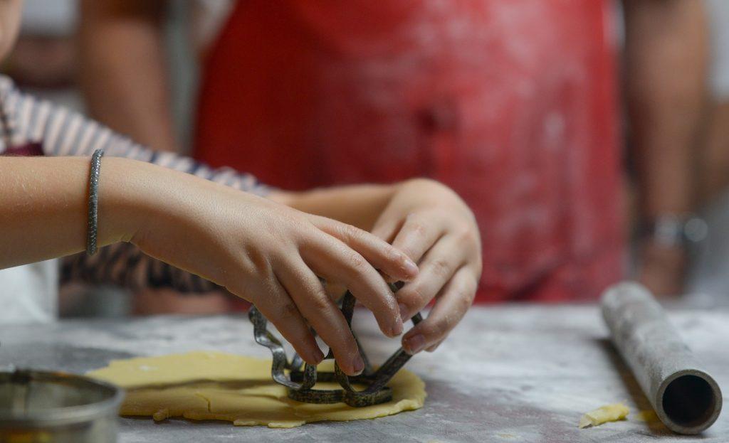 Niños amasando para ilustrar los beneficios de aprender a cocinar