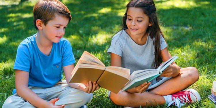 Dos niños con libros para celebrar el Día Internacional de la felicidad