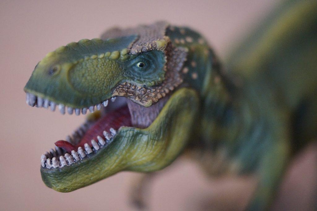 Figura de Tyrannosaurus Rex entre recursos educativos de dinosaurios