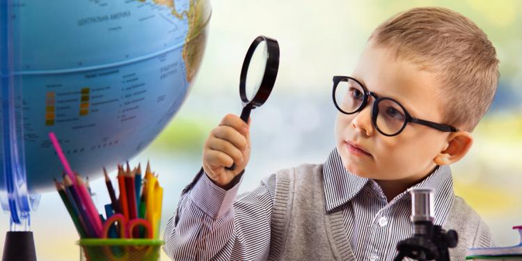 Nen mirant amb lupa una bola del món