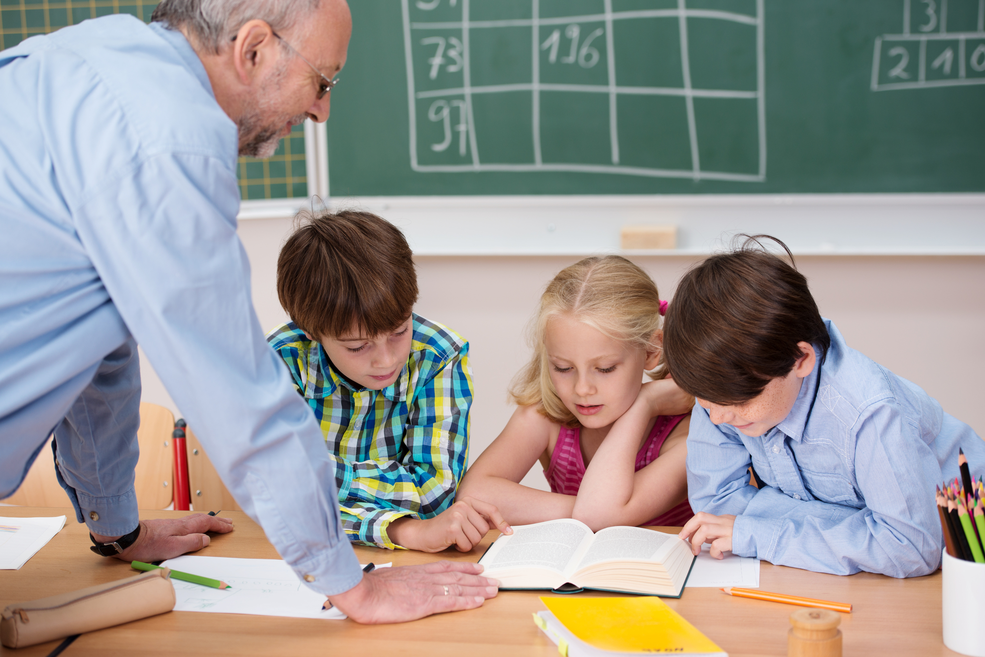 Tres niños en un escritorio con un profesor