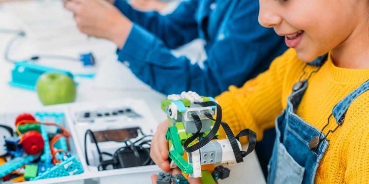 Una nena treballant sobre un invent per il·lustrar els grans inventors
