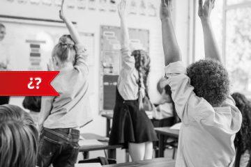 nens amb el braç alçat a una classe