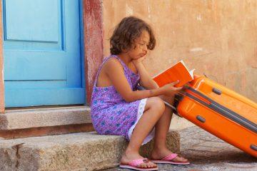Una niña con uno de sus libros para el verano y una maleta sentada en un portal de un pueblecito.