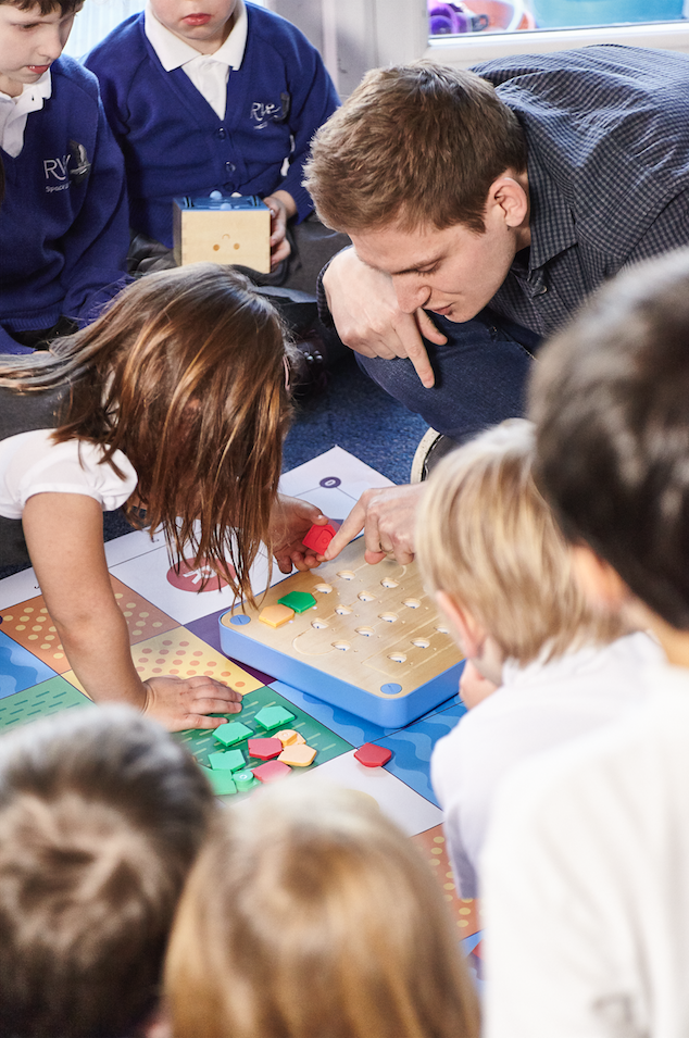 Profesor enseñando a alumnos a programar la actividad cubetto se va de vacaciones