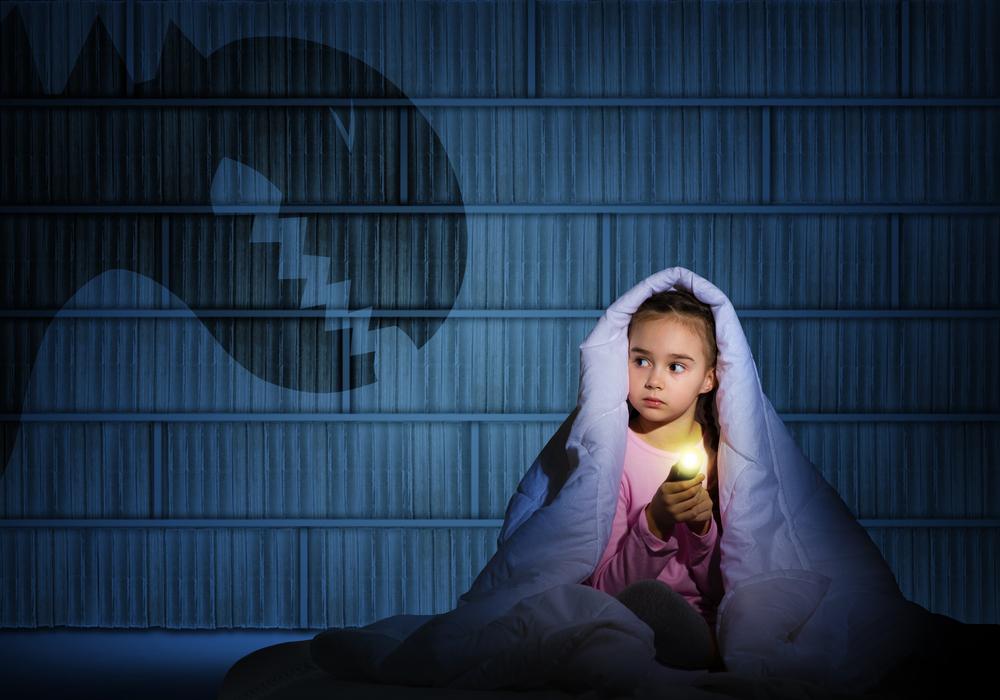 imagen de una niña con una sábana con sombra de monstruos para aprender con los monstruos