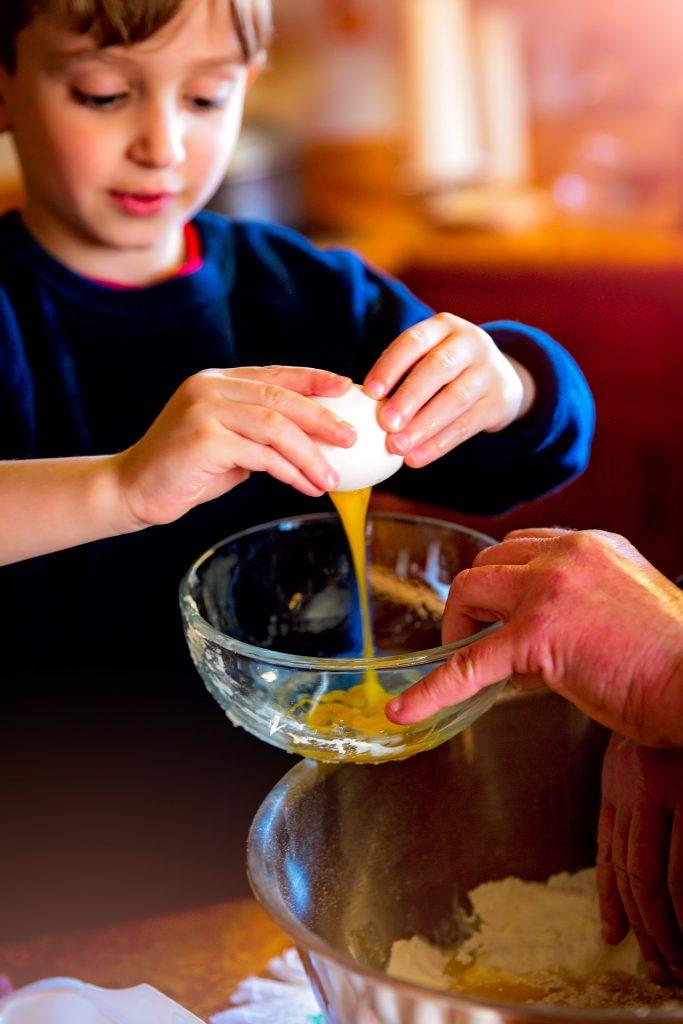 Niño rompiendo un huevo para ilustrar beneficios de aprender a cocinar