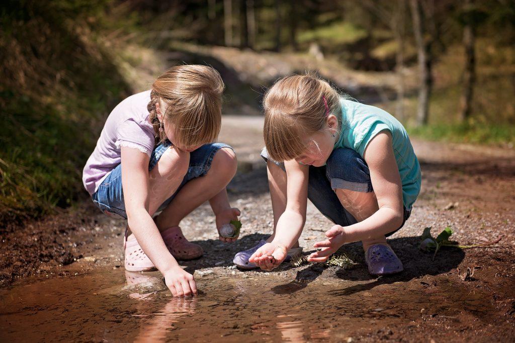 Niñas jugando en un charco en 6 actividades en la naturaleza para niños
