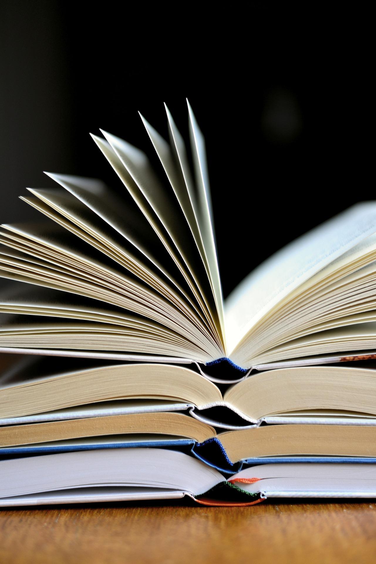 Foto de tres libros abiertos apilados para ilustrar el elogio del libro en papel
