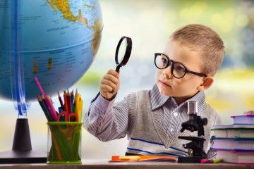 Niño con lupa y globo terràqueo para aprender las capitales