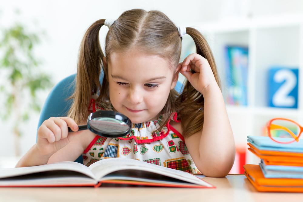 Niña mirando libro con lupa para lectura crítica