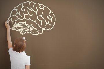 Niña dibujando un cerebro en la pizarra