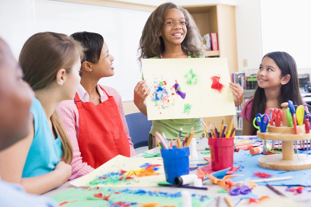 Niña enseñando un dibujo al resto de la clase para aprendizaje desde la emoción