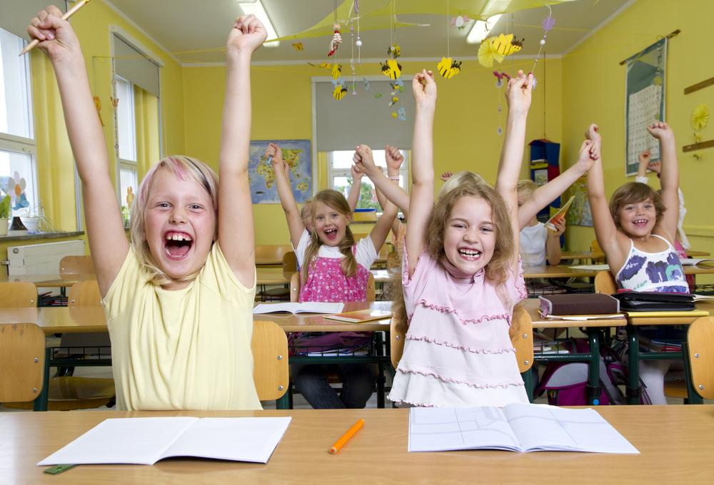niños entusiasmados con los brazos levantados para aprendizaje desde la emoción
