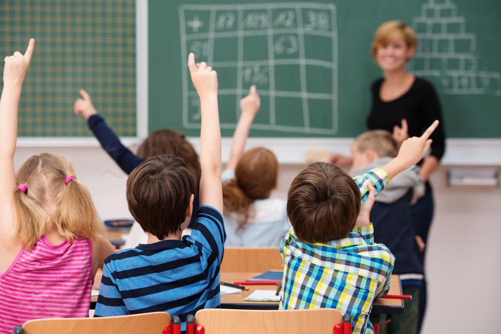 classe de niños levantando la mano con profesora al fondo para neurociencia educativa