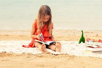 nena a la platja lelgint una elctura per a aquestes vacances