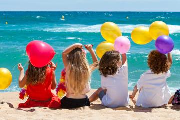 Niños en la playa con globos para felices vacaciones