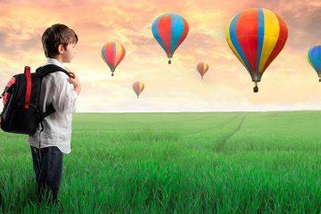Niño con un mochila observando globos aerostáticos en libros para viajar