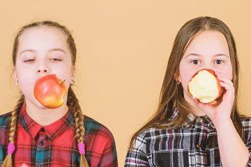 Dos niñas con una manzana para ilustrar los buenos hábitos