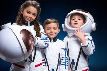 Tres niños vestidos de astronautas para ilustrar la llegada a la luna