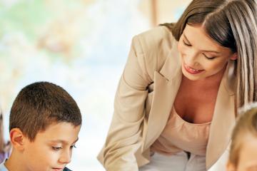 Profesora ayudando un alumno en clase para ilustrar las cualidades de un buen docente