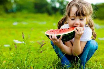 Nena menjant síndria per il·lustrar alimentació saludable