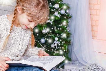 Niña leyendo delante de árbol de Navidad para aventuras mágicas