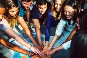 Diferentes jóvenes juntando manos para Valores educativos del Voluntariado