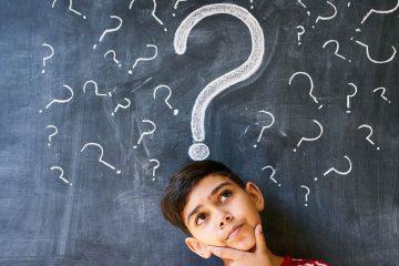 Niño pensando frente a una pizarra llena de interrogantes para ilustrar la importancia de trabajar la lógica