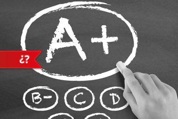 Imatge d'una ma amb guix escrivint A+ en una pissarra per a una evaluació per competències