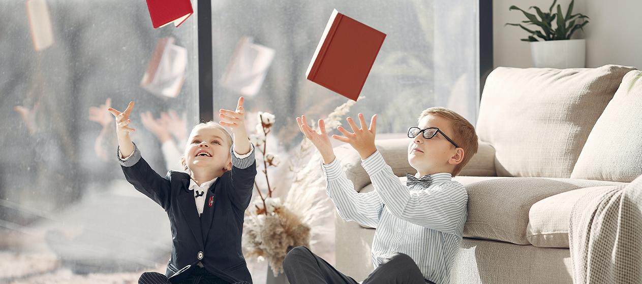 nens jugant llençant llibres per a propostes per jugar amb llibres