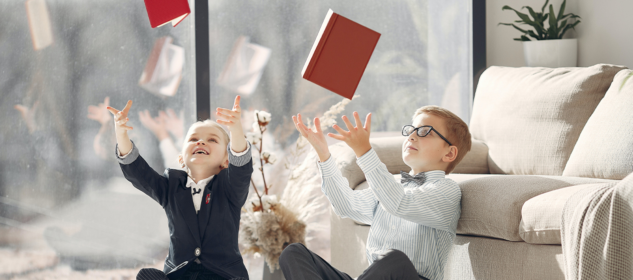 niños jugando lanzando libros