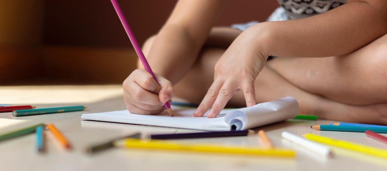 Concurso de dibujos, manos de niño pintando en libreta