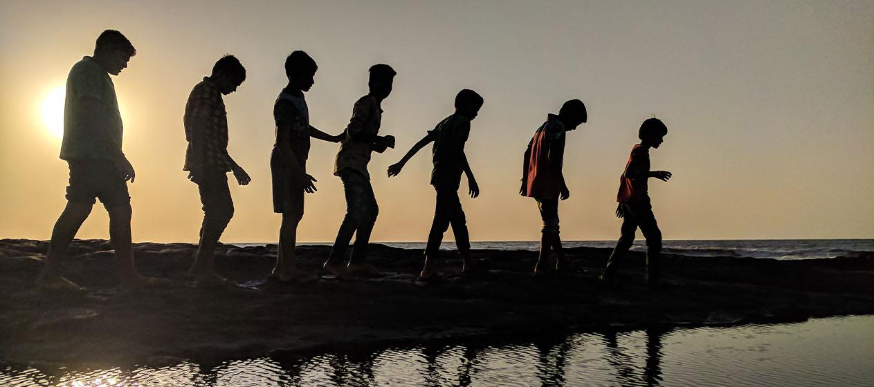 grup de nens caminant en una posta de sol per a lliçó principito